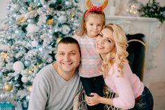 Young family on background of Christmas tree. Portrait of young happy family near Christmas tree royalty free stock photography