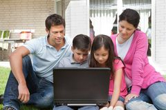 Young family in backyard using laptop. Happy young family sitting outside their house using laptop Royalty Free Stock Image