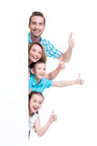 Young family with a banner showing the thumbs-up. Sign - isolated on a white background Stock Images