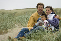 Young family at the beach. On a brisk windy day in the fall Royalty Free Stock Images