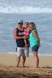 Young family at beach. Mom, dad and toddler on beach having their photo taken Royalty Free Stock Image