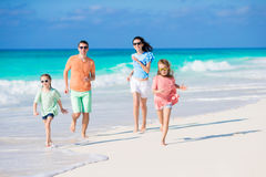 Young family on beach vacation. Young family of four on beach vacation Stock Photography