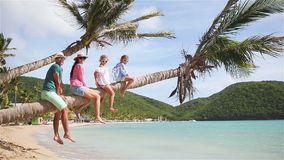 Young family on beach vacation on palm tree. Parents and kids having fun together on the coast of Caribbean on Antigua