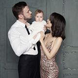 Young family with beautiful little baby in thair arms royalty free stock photography