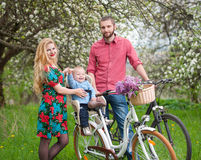 Young family on a bicycles in the spring garden. Beautiful family on a bicycles in the spring garden. Mother holding her bike and baby sitting in bicycle chair Stock Images