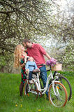 Young family on a bicycles in the spring garden Stock Photography