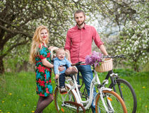 Young family on a bicycles in the spring garden. Happy family on a bicycles in the spring garden. Mother holding bike and baby sitting in bicycle chair. Against Royalty Free Stock Photo