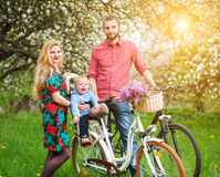 Young family on a bicycles in the spring garden Stock Photo