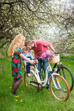 Young family on a bicycles in the spring garden. Mother holding your bike and baby sitting in bicycle chair, in the basket lay a bouquet of lilacs, against the Royalty Free Stock Images