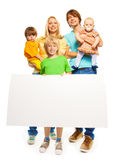 Young family with blank advertising banner. Portrait of a family standing isolated on white, mother, father, little boys and baby girl holding blank advertising Stock Image