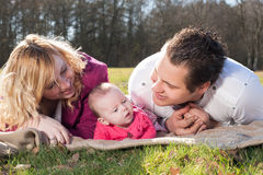 Young family on a blanket in the grass Stock Images