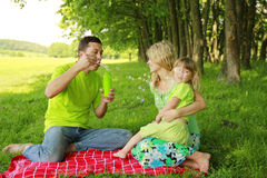Young family blowing bubbles on nature Stock Images