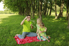 Young family blowing bubbles on nature Stock Photo