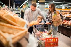 Young Family Buying Bread in Supermarket. Portrait of happy young family  shopping for groceries in supermarket together with little boy, while choosing fresh Royalty Free Stock Photo
