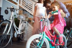 Young family buying new bicycle for little girl in bike shop. Young family buying new bicycle for happy little girl in bike shop royalty free stock photography