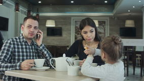 Young family in cafe. Father make a phone call while mother and daughter talking. Mother looking at him dissatisfied. stock video footage