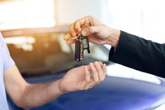 The seller in the car showroom gives the car keys to the buyer. Royalty Free Stock Photos