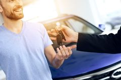 The seller in the car showroom gives the car keys to the buyer. Royalty Free Stock Photography