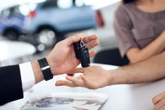 The seller in the car showroom gives the car keys to the buyer. Royalty Free Stock Images