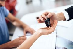 The seller in the car showroom gives the car keys to the buyer. Stock Images