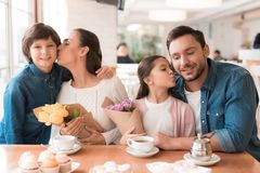 Dad and the little son are giving flowers to mother and daughter in a cafe. A young family came together in a cafe. They celebrate the holiday. Mom, dad and Royalty Free Stock Images