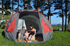 Young family camping in a tent outdoors Stock Photography