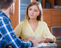 Young family cannot afford payment and discussing loan. Young family couple at desk with financial documents indoors Stock Photos