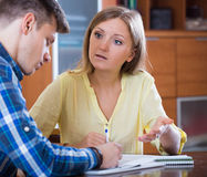 Young family cannot afford payment and discussing loan. Young family couple at desk with financial documents indoors Royalty Free Stock Images