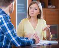 Young family cannot afford payment and discussing loan. Young family couple at desk with financial documents indoors Royalty Free Stock Photo