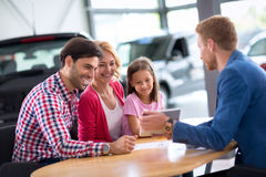 Young family  in car dealership Stock Images