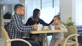 Young family in casual clothes drinking tea in cafe, talking and relaxing together. royalty free stock photography