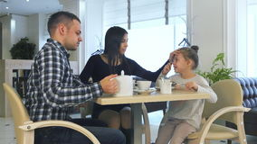 Young family in casual clothes drinking tea in cafe, talking and relaxing together. stock footage