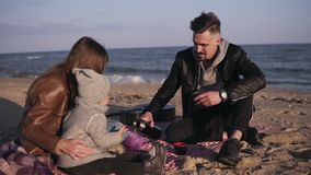 Young family in casualwear sitting on plaid by waterside and having hot drinks at picnic. Cold weather, weekend. Recreation stock video footage