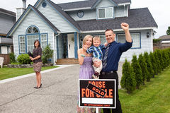 Young family celebrate new house purchase outside. A husband and wife with their young boy cheers outside their new home with the real estate agent in the stock photo