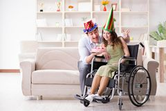 The young family celebrating birthday with disabled person. Young family celebrating birthday with disabled person Royalty Free Stock Photos