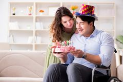 The young family celebrating birthday with disabled person. Young family celebrating birthday with disabled person Stock Photos