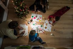 Young family celebrating Christmas making decorations Royalty Free Stock Image