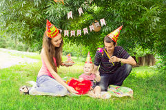 Young family celebrating the first birthday of their child in th. Young family celebrating the first birthday of their daughter on the green glade in the park royalty free stock images
