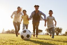 Young family chasing after a football in a park stock photo