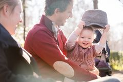 Young family with cheerful child in the park. Stock Photos