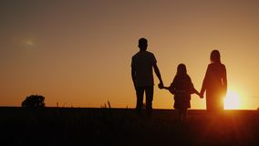 Young family with a child admiring the sunset in the field, holding hands royalty free stock photo
