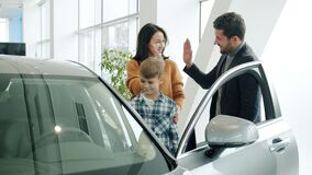 Young family with child buying car in dealership, man and woman doing high-five