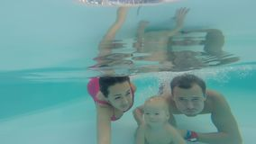A young family with a child dives under the water in an open pool. Selfi. A young family with a child dives under the water in an open pool. Selfi stock footage