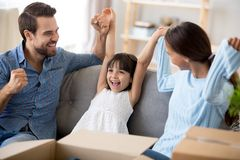 Young family with child move at new home. Happy multi-ethnic family with small girl sitting on couch in living room with carton boxes holding rising hands feels stock photography