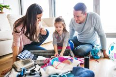Young family with a child packing for holiday. Portrait of a young happy family with a child packing for holiday at home Stock Photo