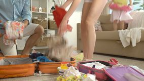 Family with child packing luggage for journey. Young family with child packing a luggage for a new journey stock video