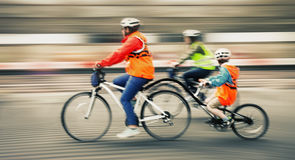 Young family with a child ride a bikes on a city streets Stock Photography