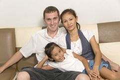 Young family with child smiling sitting on sofa Stock Photo