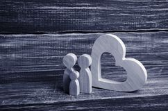 A young family with a child is standing near a wooden heart. Love and loyalty, a strong young family. Family relationships. Civil marriage. Extramarital royalty free stock photo