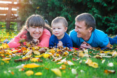 Young family with a child walks in autumn park Stock Photos